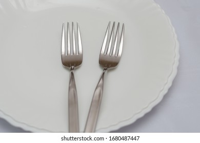 two forks on a white plate, cutlery