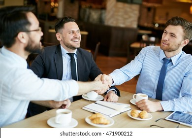Two formally dressed pleased businessmen in shirts on casual meeting in cafe sharing coffee and shaking hands in agreement over deal, another coworker in suit looking happy