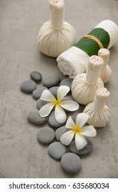 Two frangipani with gray stones with three herbal ball ,rolled towel on grey background.