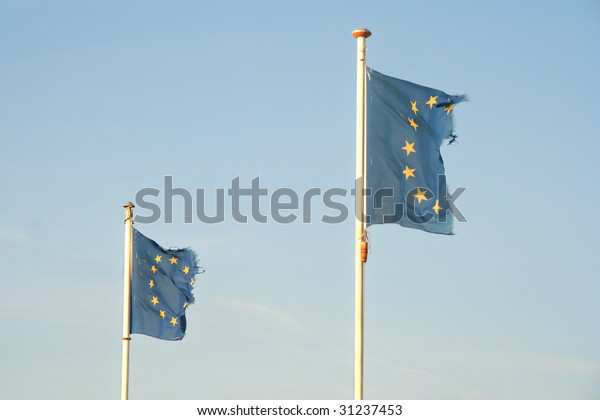 Two frayed European Union flags