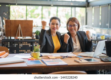 Two freelancer beautiful asian woman happy success business project with digital laptop computer at workplace coffee shop. Business concept