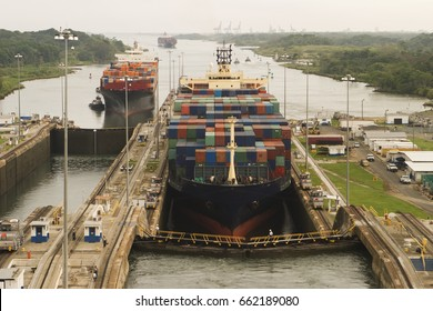 Two freighters, led by tugboats, are starting to transit the Panama Canal at the Gatun Locks on the Atlantic side. These container ships are fully loaded with cargo heading west towards the Pacific.