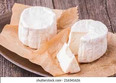 Two french goats cheeses on wooden background