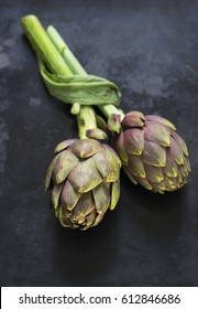 Two fresh artichokes on a dark textural background. Selective focus