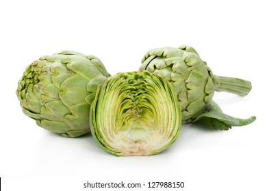 Two fresh artichokes with stem and leaf and a half showing the heart. Isolated.