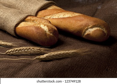 Two fresh baguettes lying on a brown burlap mat with wheat