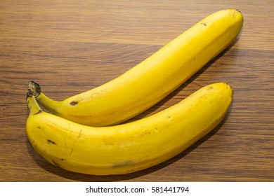 Two fresh bananas on a wooden background.