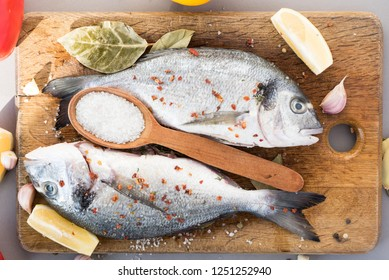 Two fresh big sea fish (dorado), sprinkled with coarse salt and flavored seasonings with a wooden spoon with salt and lemon pieces on a dark wooden board. View from above