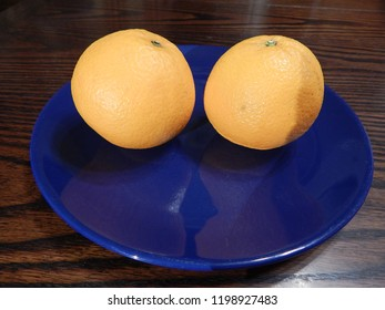 Two fresh bright yellow oranges on a blue plate