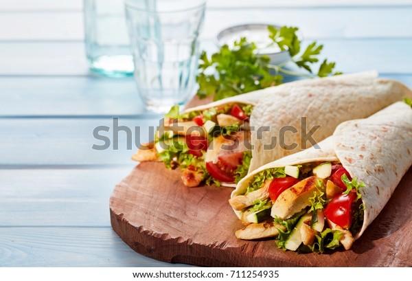 Dvě čerstvé kuřecí a salátové tortilla zábaly na dřevěné prkénko s brýlemi v pozadí