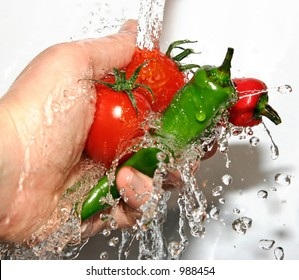 Two fresh chilies being rinsed with Two vine tomatoes - great details of water droplets