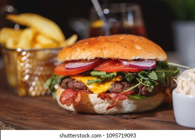 Two fresh classic burgers with beef, cheese, bacon, onion, tomato and lettuce on wooden table.