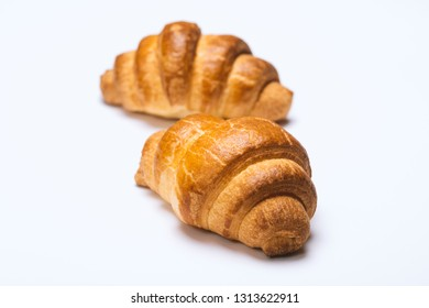 two fresh croissants on white background
