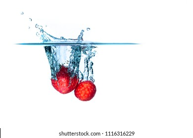 Two fresh and delicious red strawberries isolated on a white background. Red strawberry dropping in water and creating a splash. The concept of healthy eating, consuming fruit.