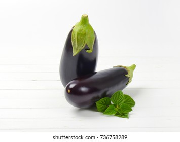 two fresh eggplants and sage on white wooden background