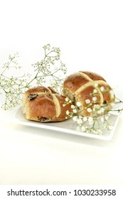Two fresh hot cross buns a traditional Easter holiday treat shot selective focus with Gypsophilia flowers with generous accommodation for copy space. Suitable image for your breakfast menu cover art.