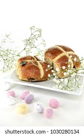 Two fresh hot cross buns a traditional Easter holiday treat shot with selective focus with Gypsophilia flowers and candy Easter eggs with generous accommodation for copy space.