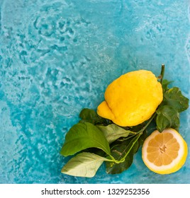 Two fresh lemon with leaves on a blue ceramic surface. Top view.