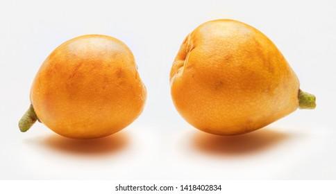 Two fresh loquats (medlars). Isolated on white background. Close-up.