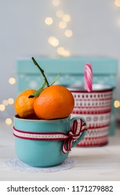 two fresh mandarins in a blue cup and christmas bin with christmas cane on bokeh background
