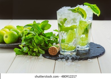 Two fresh mojitos cocktail on wooden background. Mojitos with mint leaves, lime and ice. Drink making tools and ingredients for cocktail.