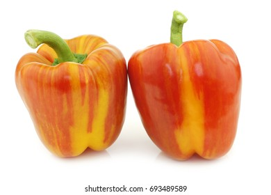 "two fresh orange and yellow ""enjoya""  bell peppers (capsicum) on a white background"