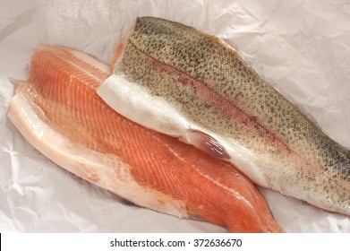 Two fresh rainbow trout fillets, one flesh side up and one skin side up, on greaseproof paper ready to be cooked for a healthy seafood dinner