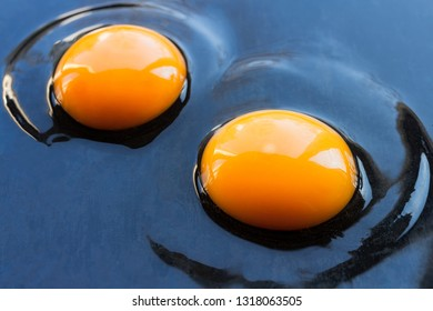 Two fresh raw chicken eggs spilled on a dark pan
