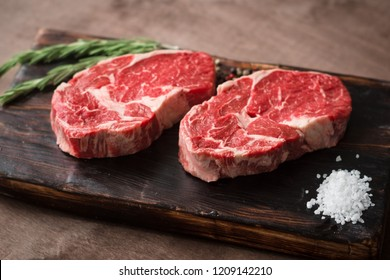 Two fresh raw rib-eye steak on wooden Board on wooden background with salt, pepper and rosmary in a rustic style