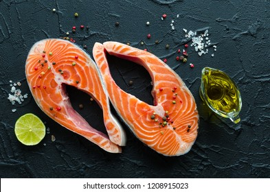 Two fresh raw salmon steaks with pepper corns, salt, lemon and olive oil on black background. Healthy food, diet concept. Preparation for cooking fish with spices. Top view.