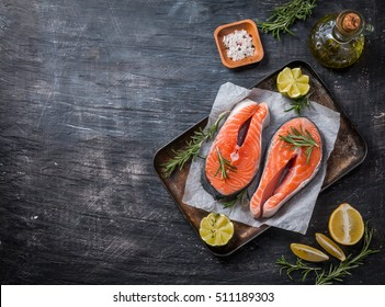 Two fresh raw salmon steaks on paper with salt, peppers, lemon, and rosemary on black background, top view