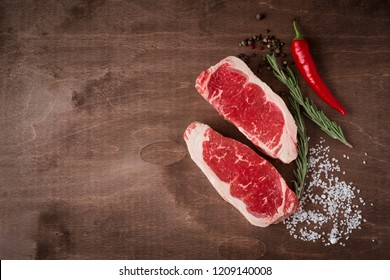 Two fresh raw strip loin steak on wooden Board on wooden background with salt, pepper and rosmary in a rustic style, top view