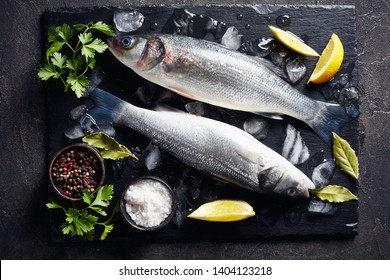 two fresh raw whole sea bass on slate plate with lump ice, lemon slices, spices and herbs, view from above, close-up, flatlay,