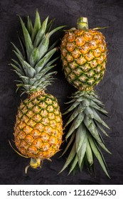 Two Fresh ripe pineapple on dark background, vertical composition , top view