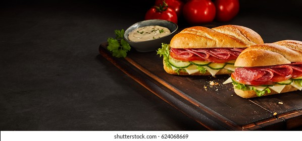Two fresh sandwiches made with meat, vegetables and cheese with a saucer full of dipping sauce