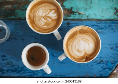 two fresh tasty cappuccino coffee cups with latte art on it and one espresso cup with beautiful tiger crema on the coffee table
