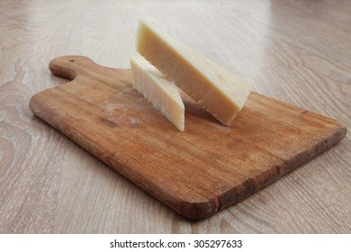 two fresh triangle french delicacy parmesan cheese pieces on wooden cut board over table
