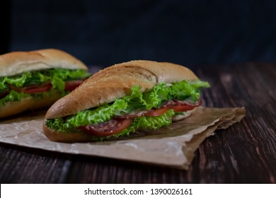 Two fresh underwater sandwiches with sausage, cheese, bacon, tomatoes, lettuce, cucumbers and onions on a dark wooden background