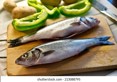 Two fresh whole uncooked cleaned sea bass on a wooden board with sliced green bell peppers being prepared for a delicious seafood dinner