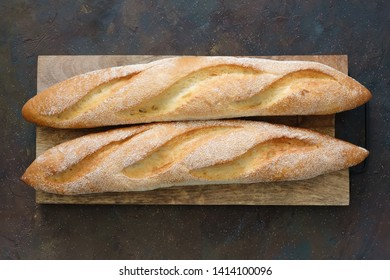 Two freshly baked baguettes on cutting board. Top view.