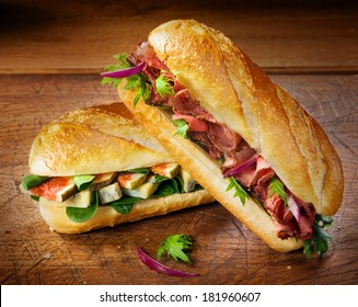 Two freshly baked crisp crusty baguettes filled with figs, spinach and blue cheese and gourmet cold roast beef for a delicious takeaway or savory lunch