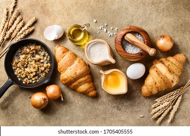 Two freshly baked onion croissants with ingredients for cooking - fried onion in cast iron pan, raw eggs, flour, salt, jug of olive oil and wheat spikes over beige concrete background