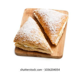 Two  freshly baked turnovers with white cream isolated on white