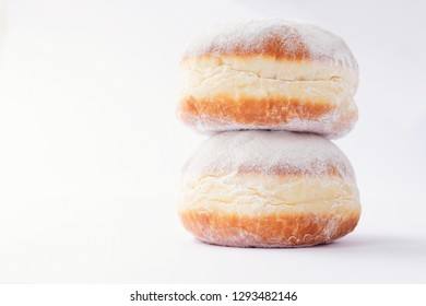 Two freshly made doughnuts, stack on top of each other, filled with jam and covered in powdered sugar on a white background