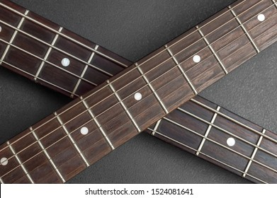 Two fretboard of guitar crossed on black. Close up.Abstract music background.