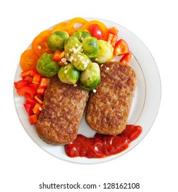 Two fried cutlets with vegetables over white background