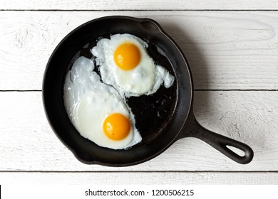 Two fried eggs in cast iron frying pan isolated on white painted wood from above.