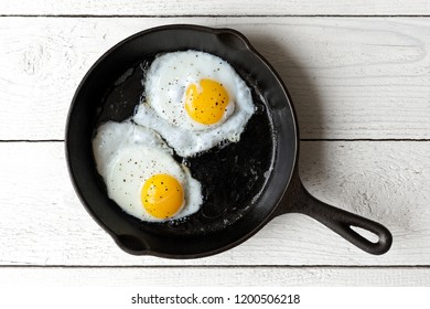 Two fried eggs in cast iron frying pan sprinkled with ground black pepper. Isolated on white painted wood from above.