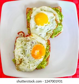 two fried eggs on avacado guacamole and brown toast on a white square shape plate, red place mat from above