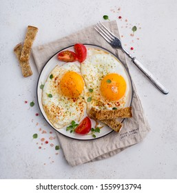 Two fried eggs on a plate, shot from above